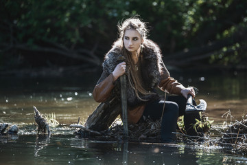 Viking woman with sword and hammer wearing traditional warrior clothes in a deep mysterious forest.