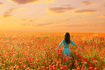 Woman walking in red poppies meadow at sunset.
