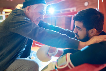 Confident senior man training bearded young boxer and motivating him for work.