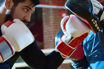 Side view of serious man in boxing gloves practicing with trainer wearing focus mitts.
