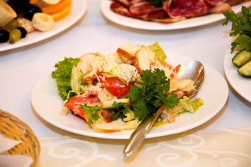 Salad with tomatoes, chicken, croutons and greens in a white plate with a spoon, on a табл.