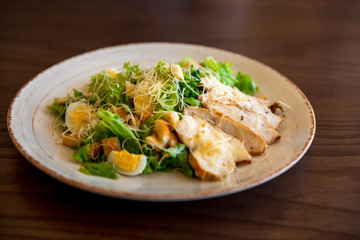 Fresh summer salad Ceasar with eggs, lettuce, chicken and parmesan cheese on white plate on wooden background; healthy concept; side view