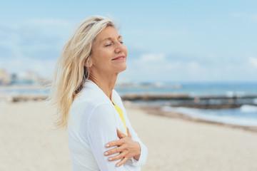 frau steht entspannt am strand und genießt mit geschlossenen augen