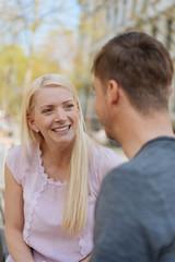 blonde junge frau schaut ihren freund lächelnd an