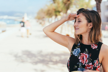 attraktive frau im blumenkleid steht am strand und schaut auf das meer