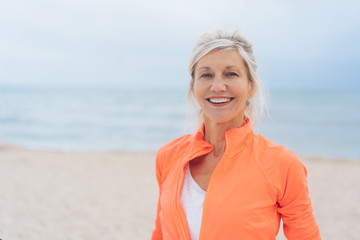 lächelnde best-agerin mit sportoutfit am strand