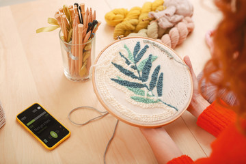 Inventive housewife. Inventive enthusiastic housewife feeling creative while embroidering nice little picture for kitchen