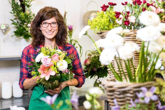 Freundlich lächelnde Floristin mit frisch gebundenem Blumenstrauss