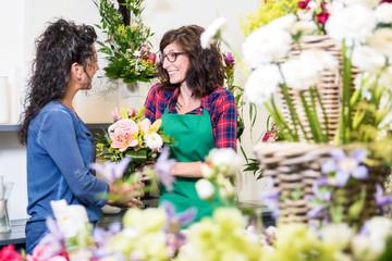 Freundlich lächelnde Floristin verkauft einer Kundin einen Blumenstrauss