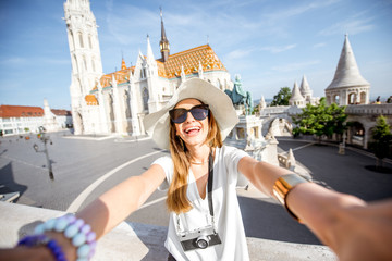 Young woman tourist making selfie photo standing in front of the famous Mattias church in Budapest, Hungary