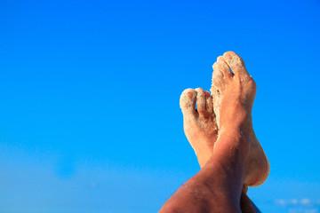 Sandy men feet in the air