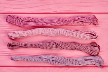 Set of threads for embroidery. Four bunches of colorful threads for embroidery on pink wooden background, top view.