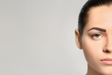 Young woman with permanent eyebrows makeup on grey background