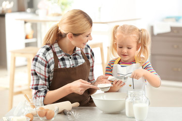 Mother with daughter making dough together in kitchen