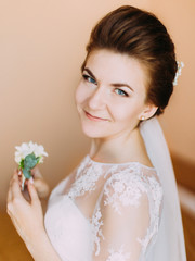 Portrait of the smiling bride with the wedding mini-bouquet.