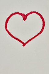 Red heart drawn with lipstick. Shape of heart drawn by lipstick on light background, copy space.