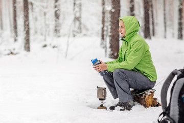 Happy woman cooking near winter tent camp in the snow forest.