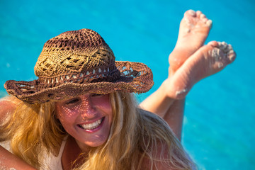 Blond woman lies with hat on the sandy beach