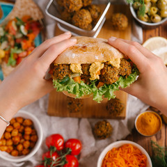 Woman holding burger with falafel balls, hummus and vegetables