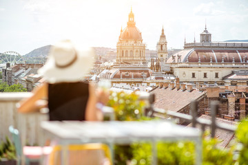 Woman enjoying great cityscape view from the terrace on the old town with saint Stephen cathedral in Budapest city, Hungary. Woman is out of focus Fototapete