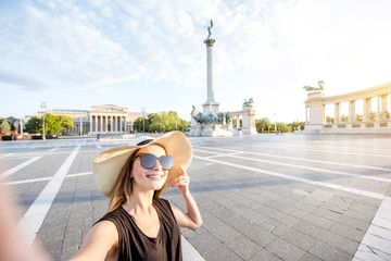 Young woman tourist making selfie photo on the Heroes square traveling in Budapest city, Hungary