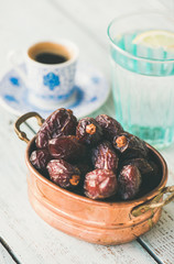 Traditional muslim food for Ramadan iftar meal. Dates in copper bowl, glass of water and coffee over wooden table.