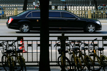 A car believed to be carrying North Korean leader Kim Jong Un drives down Chang'an Avenue towards Tiananmen Square in Beijing