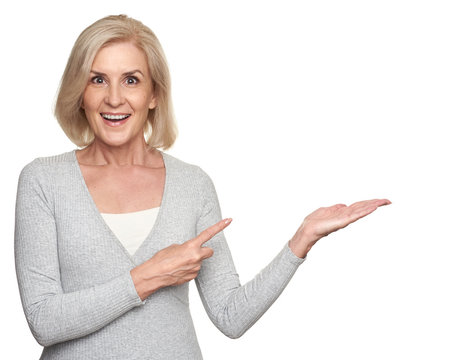 middle aged lady pointing to copyspace