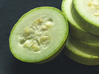 Chopped fresh green zucchini on a black background