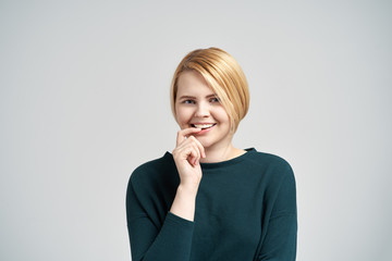 Indoor portrait of delighted European attractive female smiles happily, keeps fore finger near mouth, glad to hear good announcement, wears casual outfit, stands indoor against white background