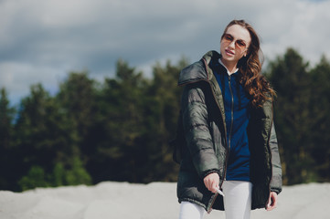 Teen girl loves outdoor activities, she walks through the mountain landscape dressed in a warm jacket and backpack