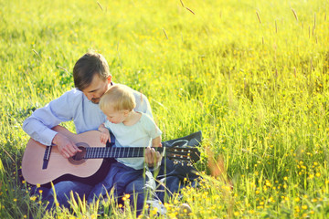 Father teaching his son to play guitar outdoor. Time together dad and son. Copy space