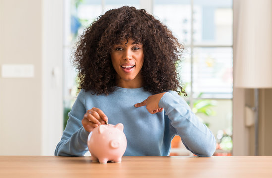African american woman saves money in piggy bank with surprise face pointing finger to himself