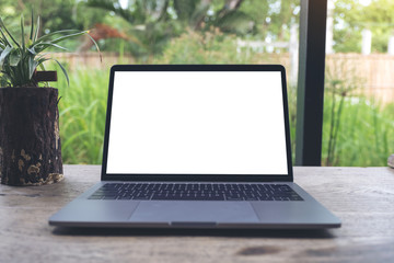 Mockup image of laptop with blank white desktop screen on vintage wooden table with nature background