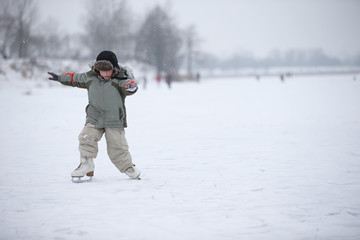 The child learns to skate on the lake. A boy ice skating on an ice river on a snowy winter day