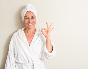Beautiful middle age woman, wet hair wearing a towel doing ok sign with fingers, excellent symbol