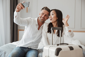 Happy young couple taking selfie with mobile phone