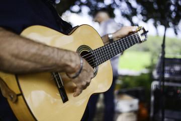 closeup detail hand playing folk guitar outdoor summer festival