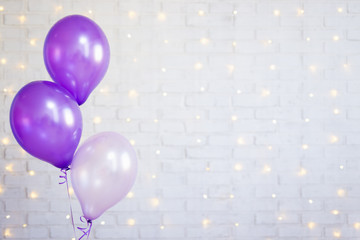 birthday party concept - air balloons over brick wall background with lights