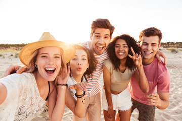 Group of happy young friends in summer clothes taking selfie, while standing at the beach during holiday on nature