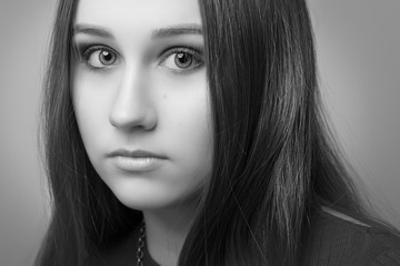 Girl with flowing hair and makeup on a gray background close-up. Black and white image.