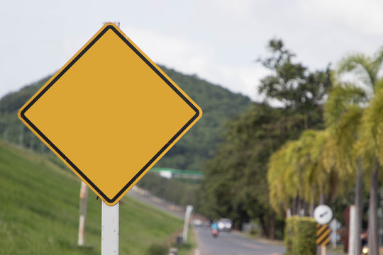Empty yellow traffic sign on blur traffic road with colorful light abstract background.