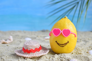 Creative minimal summer idea. Lemon citrus hipster in pink sunglasses and bamboo hat on sand. Tropical beach concept. Creative art. Fun party Mood. Copy space