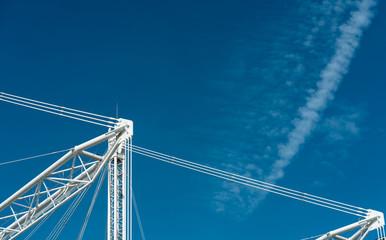 Closeup building crane against blue sky and clouds.