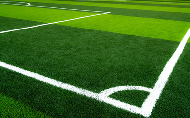 Green grass soccer field. Empty artificial turf football field with white line. View from the corner of soccer field. Sport background