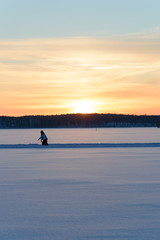 Ice skating in skandinavien winter sunset on frozen lake