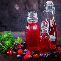 Drink Summer from Mix Berries Decorated with Green Mint. Compote in Glass Bottles. Old dark Background. Superfoods and healthy lifestyle or detox diet food concept.