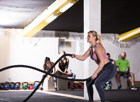 athlete woman doing battle ropes cross fitness exercise