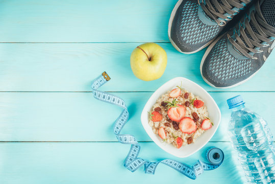 Sneakers, bottle of water, tape measure, oatmeal with strawberry and raisins and apple on blue background. Healthy lifestyle, fitness, food
