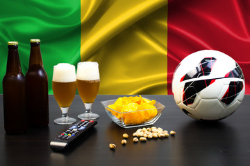 2 bottles of beer, 2 glasses of beer next to the football on the background of the flag of Senegal.